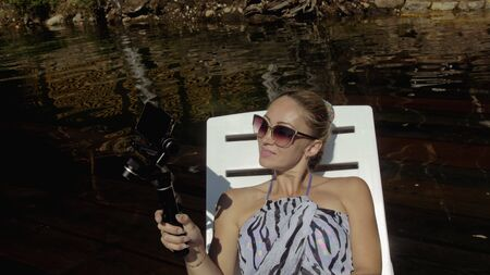 Woman shooting on handheld film gimbal stabilization for smartphone. Girl rest, relax, lie sunbed on pier in sunglasses, make selfie. Lady blogger broadcast video blogging vlogging. Take photo video. Imagens