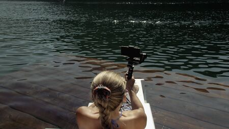 Woman shooting on handheld film gimbal stabilization for smartphone. Girl rest, relax, lie sunbed on pier in sunglasses, make selfie. Lady blogger broadcast video blogging vlogging. Take photo video. 스톡 콘텐츠