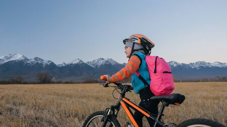 One caucasian children walk with bike in wheat field. Little girl walking black orange cycle on background of beautiful snowy mountains. Biker stand with backpack and helmet. Mountain bike hardtail. Banco de Imagens