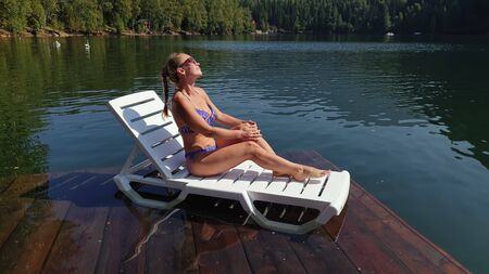 Woman sit on a sunbed in sunglasses and swimming suit. Girl rest on a flood wood underwater pier. The pavement is covered with water in lake. Background are mountain and forest. Swimwear bikini blue.