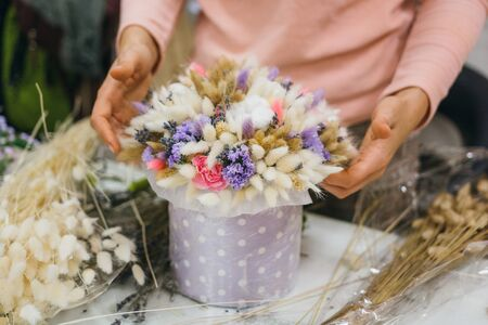 Colorful bouquet of different dried flowers deadwood flowers in the hands of a florist woman. Rustic flower background. Craft bouquet of flowers. The process of making a bouquet.