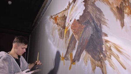 Artist designer draws an eagle on wall. Craftsman decorator paints picture with acrylic oil color looking at sketch in phone. Painter painter dressed in paint coat. Indoor. Dark magic cinematic look. Stok Fotoğraf