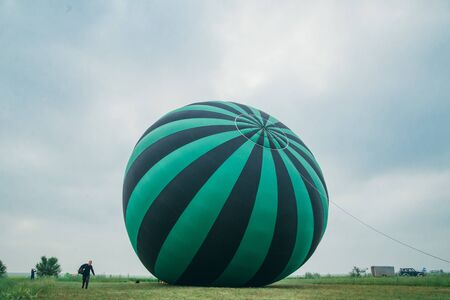 Inflating, unpack and flying up hot air balloon watermelon. Burner directing flame into envelope. Take off aircraft fly in morning blue sky. Start hot air burning to inflate gas fire to air balloon.