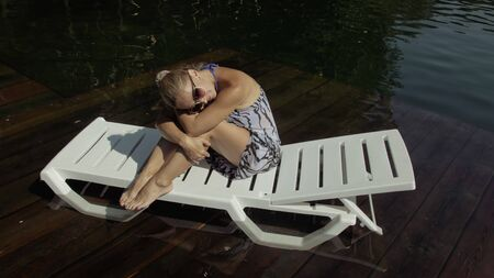 Woman lie on a sunbed in sunglasses and a boho silk shawl. Girl rest on a flood wood underwater pier. The pavement is covered with water in the lake. In the background are mountain and a forest. Reklamní fotografie