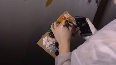 Artist designer draws an eagle on wall. Craftsman decorator paints picture with acrylic oil color looking at sketch in phone. Painter painter dressed in paint coat. Indoor. Dark magic cinematic look. Stock Photo