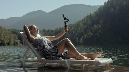 Frau schießt auf Handheld-Film-Gimbal-Stabilisierung für Smartphone. Mädchen ruhen sich aus, entspannen Sie sich, liegen Sie mit Sonnenbrille auf dem Pier, machen Sie Selfie. Lady Blogger sendet Video-Blogging-Vlogging. Fotovideo aufnehmen.