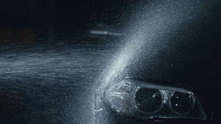 Lavado de faros de coche. Lavado de la carrocería del vehículo moderno con agua de manguera de lavado a alta presión. Linterna frontal de vidrio para automóvil, ojos de ángel en gotas. Cerca del reflector de un automóvil negro mientras se limpia.