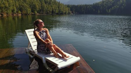 Woman lie on a sunbed in sunglasses and a boho silk shawl. Girl rest on a flood wood underwater pier. The pavement is covered with water in the lake. In the background are mountain and a forest.