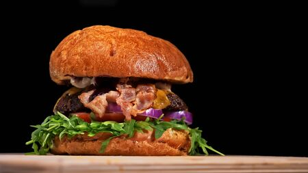 Craft burger is cooking on black background. Consist: sauce, arugula, tomato, red onion, bacon, red currant sauce, ricotta cottage fresh cheese, air bun and marble meat beef. Not made ideal. Looks real, loving hand made.
