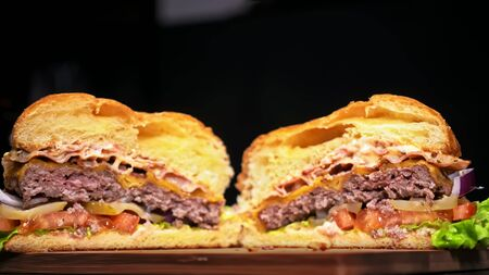 Cut craft burger is cooking on black background in black food gloves. Consist: sauce, lettuce, tomato, red onion, pickle, cheese, bacon, air bun and marbled meat beef. Not made ideal. Looks real, loving hand made. Stock Photo