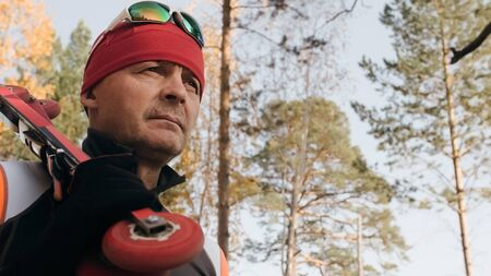 Training an athlete on the roller skaters. Biathlon ride on the roller skis with ski poles, in the helmet. Autumn workout. Roller sport. Adult man riding on skates.The athlete goes and holds sports equipment in his hand.