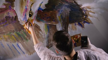 Artist designer draws an eagle on wall. Craftsman decorator paints picture with acrylic oil color looking at sketch in phone. Painter painter dressed in paint coat. Indoor. Dark magic cinematic look.