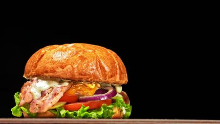 Craft burger is cooking on black background. Consist: sauce, lettuce, tomato, red onion, cucumber, cheese, bacon, air bun and of chicken. Not made ideal. Looks real, loving hand made.