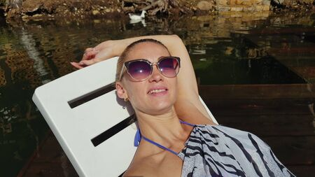 Woman shooting self portrait. Take photo and video on smartphone. Girl rest, relax, walk in sunglasses, make selfie. Lady blogger broadcast video blogging vlogging. Sunbed on pier. Pov view. Banco de Imagens