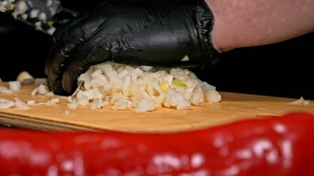 The cook makes salsa. Salsa for burgers on hot Mexican hot recipes. It is prepared from a tomato, red chili peppers, onions, white onions. All chalks are cut with a knife.