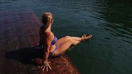 Woman sit on a pier in sunglasses and swimming suit. Girl rest on a flood wood underwater pier. The pavement is covered with water in lake. Lady in the water and splashes feet. View from above. Stockfoto