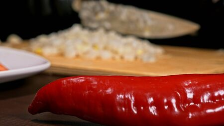 The cook makes salsa. Salsa for burgers on hot Mexican hot recipes. It is prepared from a tomato, red chili peppers, onions, white onions. All chalks are cut with a knife. Archivio Fotografico
