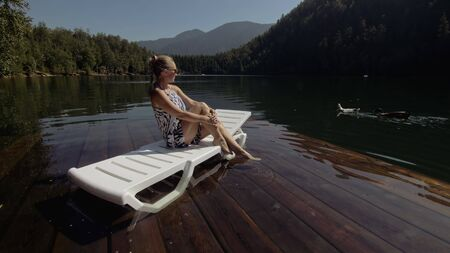 Woman lie on a sunbed in sunglasses and a boho silk shawl. Girl rest on a flood wood underwater pier. The pavement is covered with water in the lake. In the background are mountain and a forest. Stock Photo