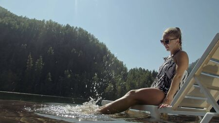 Woman lie on a sunbed in sunglasses and a boho silk shawl. Girl rest on a flood wood underwater pier. The pavement is covered with water in the lake. In the background are mountain and a forest. Imagens