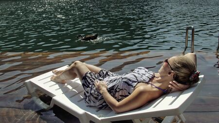 Woman lie on a sunbed in sunglasses and a boho silk shawl. Girl rest on a flood wood underwater pier. The pavement is covered with water in the lake. In the background are mountain and a forest. Stock fotó