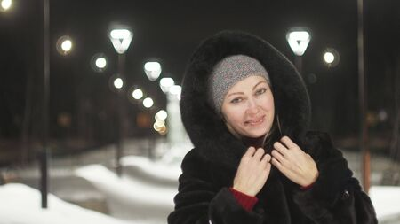 Pretty woman walking along the black fur coat. Outdoor. Girl walks on a winter night among the street lights of the city. Snow park with garlands. Beautiful sensual happy smile. Stok Fotoğraf