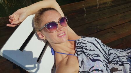Woman shooting self portrait. Take photo and video on smartphone. Girl rest, relax, walk in sunglasses, make selfie. Lady blogger broadcast video blogging vlogging. Sunbed on pier. Pov view. Imagens