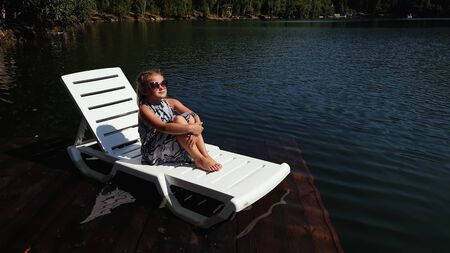 Kid girl lie on a sunbed in sunglasses and a boho silk shawl. Child rest on a flood wood underwater pier. The pavement is covered with water in the lake. In the background are mountain and a forest.