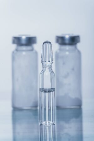 Glass medical ampoule vial for injection. Medicine is liquid sodium chloride with of aqueous solution in ampulla. Close up. Bottles ampule multicolor on background color and water. Human plasma. Stok Fotoğraf