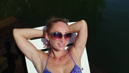 Woman lie on a sunbed in sunglasses and swimming suit. Girl rest on a flood wood underwater pier. The pavement is covered with water in lake. Close up self portrait selfie. Swimwear bikini blue.