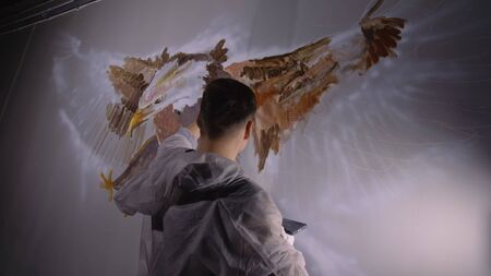 Artist designer draws an eagle on wall. Craftsman decorator paints picture with acrylic oil color looking at sketch in phone. Painter painter dressed in paint coat. Indoor. Dark magic cinematic look. 写真素材