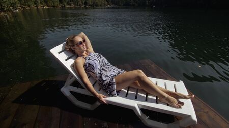 Woman lie on a sunbed in sunglasses and a boho silk shawl. Girl rest on a flood wood underwater pier. The pavement is covered with water in the lake. In the background are mountain and a forest. Banco de Imagens