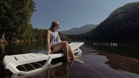 Woman lie on a sunbed in sunglasses and a boho silk shawl. Girl rest on a flood wood underwater pier. The pavement is covered with water in the lake. In the background are mountain and a forest. 스톡 콘텐츠