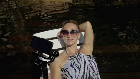 Woman shooting on handheld film gimbal stabilization for smartphone. Girl rest, relax, lie sunbed on pier in sunglasses, make selfie. Lady blogger broadcast video blogging vlogging. Take photo video. Фото со стока