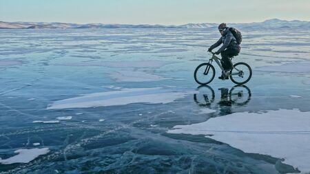 Man is riding bicycle on the ice. Ice of the frozen Lake Baikal. Rider is dressed in black down jacket, cycling backpack, helmet. Tires on covered with special spikes. Traveler boy is ride cycle. Banco de Imagens