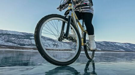 Woman is riding bicycle on the ice. Girl is dressed in a silvery down jacket, cycling backpack and helmet. Ice of the frozen Lake Baikal. Tires on bike are covered with spikes. Traveler is ride cycle. Banco de Imagens