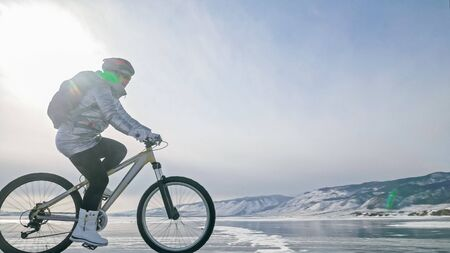 Woman is riding bicycle on the ice. Girl is dressed in a silvery down jacket, cycling backpack and helmet. Ice of the frozen Lake Baikal. Tires on bike are covered with spikes. Traveler is ride cycle. Banque d'images - 138395385