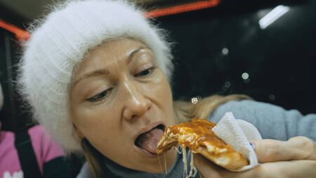 Girl eat pizza cheese four. Close up of young woman mouth greedily eating pizza and chewing in outdoor restaurant. Human hands taking pieces slices of hot tasty italian pizza from open box. Junk food. Фото со стока