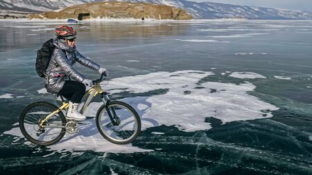 Woman is riding bicycle on the ice. Girl is dressed in a silvery down jacket, cycling backpack and helmet. Ice of the frozen Lake Baikal. Tires on bike are covered with spikes. Traveler is ride cycle. Stockfoto