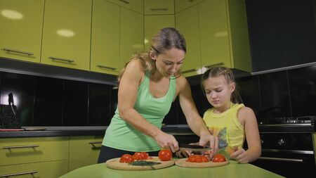 Mother teaching daughter smart girl learning to cook. Young mistress children to cook a Neapolitan egg fried omelette from salame affumicato sausage. Modern Built In Kitchen Appliances.