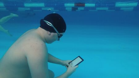 The guy is reading an electronic book underwater. This is a special waterproof electronic device. You can read the text and show signs directly underwater. 版權商用圖片