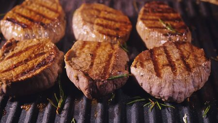 Delicious juicy meat steak cooking on grill. Aged prime rare roast grilling tenderloin fresh marble tenderness beef. Prime beef fry on electric roaster, rosemary, black pepper, salt. Slow motion. Banco de Imagens - 142968701