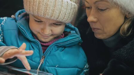 Attractive caucasian mother and daughter using smartphone sitting in winter cafe in jacket, hat. Advanced little child girl shows and explains to mom woman on smartphone, touching and watching.