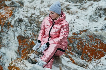 Woman is sitting in the hill. Traveler is walking in top mountain. Beautiful girl is dressed in stylish pink down jacket. Explorer looks afar, on a beautiful sky. Magic purest place in nature. Stock Photo