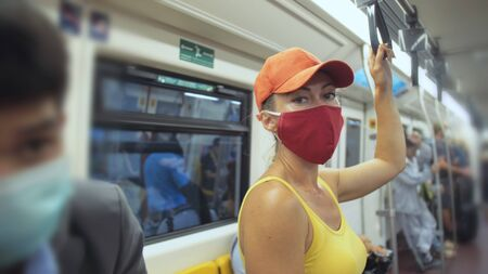 Woman travel caucasian ride at overground train airtrain with wearing protective medical red mask. Girl tourist at airtrain with respirator. Pandemic virus Coronavirus covid-19. People in mask. Stock fotó