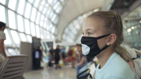 Children girl kid caucasian at airport with wearing protective medical mask on head against background of plane. Concept health virus protection coronavirus epidemic sars-cov-2 covid-19 2019-ncov. Stock fotó