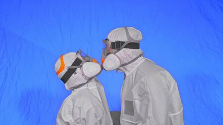 Doctor man and woman in protective costume suit, gas protect medical spray paint mask. Love couple kiss and hug, health worker in respirator. Health virus protection coronavirus epidemic covid-19.