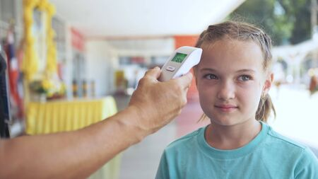 Temperature check at a supermarket of little girl, grocery store with thermal imaging camera installed. Image monitoring scanner to monitor the body temp of visitor child baby. Coronavirus Covid-19. Standard-Bild