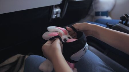 Little girl caucasian at plane with wearing protective medical mask. Child baby tourist at aircraft with respirator play with a soft toy. Coronavirus epidemic sars-cov-2 covid-19 2019-ncov.