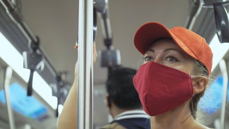 Woman travel caucasian ride at overground train airtrain with wearing protective medical red mask. Girl tourist at airtrain with respirator. Pandemic virus Coronavirus covid-19. People in mask.