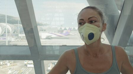 Woman caucasian at Suvarnabhumi Airport with wearing protective medical mask on head against background of plane. Concept health virus protection coronavirus epidemic sars-cov-2 covid-19 2019-ncov. Standard-Bild - 143937727